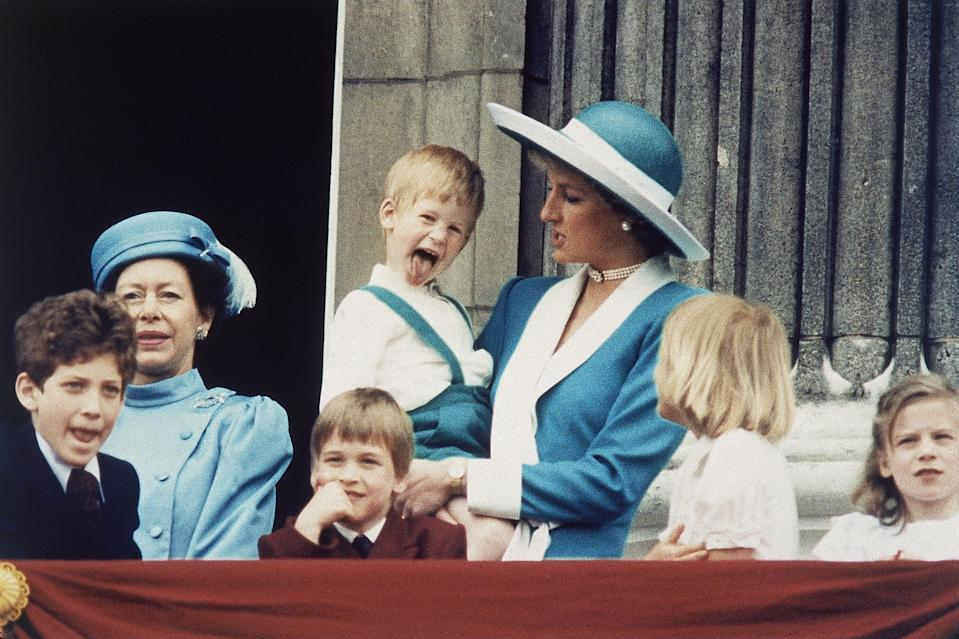 Prince Harry sticks out his tongue for the cameras on the balcony of Buckingham Palace in London, England on June 11, 1988, following the Trooping of the Colour. Princess Diana holds Harry, as a smiling Prince William sits in front, and Lady Gabriella Windsor is seen on the left.
