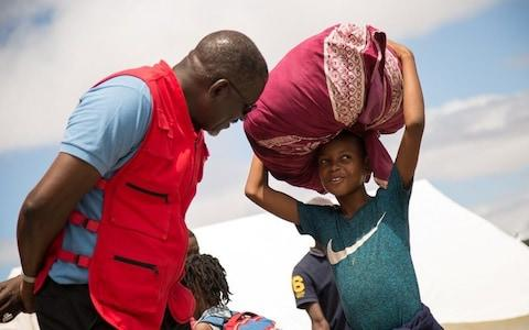 Secretary General of International Federation of Red Cross and Red Crescent Societies (IFRC), Elhadj As Sy talks with a survivor of Cyclone Idai, at an evacuation centre in Beira, Mozambique - Credit:  Reuters