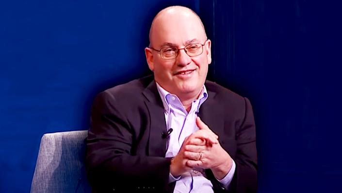 Steve Cohen treated art in chair blue background hands clasped