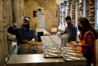 Volunteers prepare a charity Ramadan dinner in the cloister at Santa Anna church in Barcelona