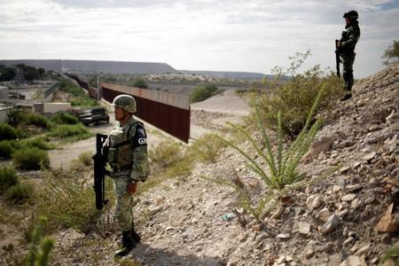 FILE PHOTO - Soldiers assigned to the National Guard keep watch near a section of the border fence between Mexico and U.S. as seen from Anapra neighborhood in Ciudad Juarez