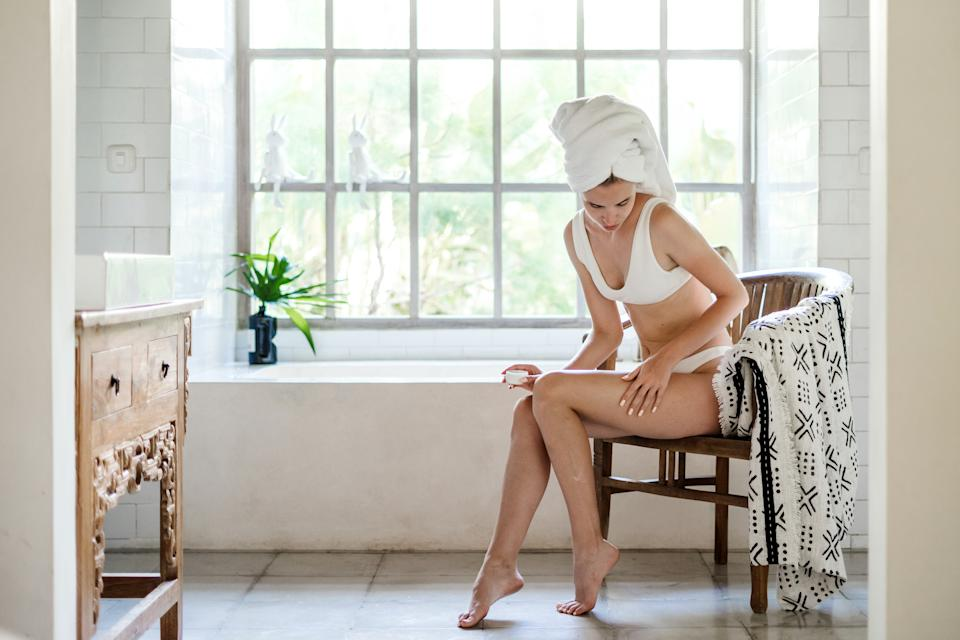 Young adult girl with towel on head sitting on chair in white bathroom, applying soft natural cream on legs, making skin and body care procedure
