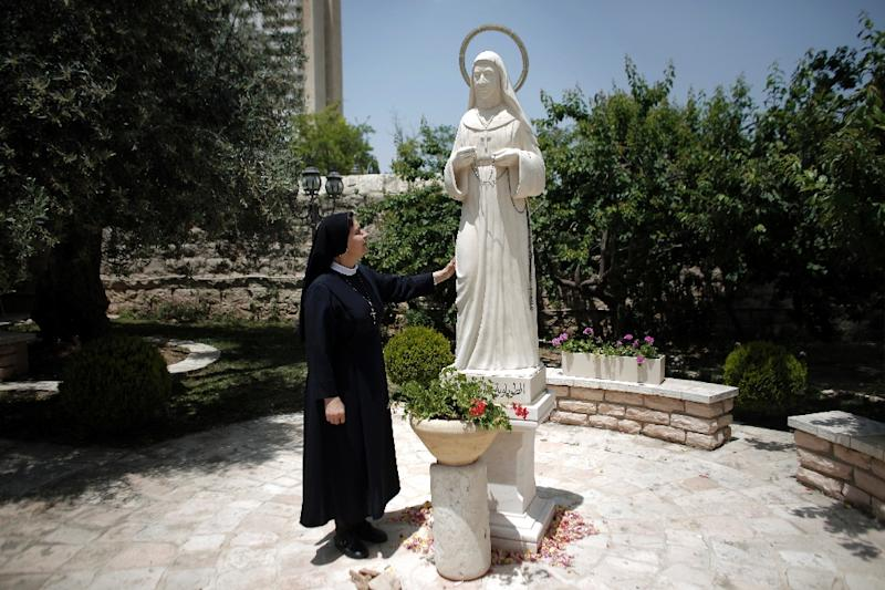 A nun looks at the statue of Marie Alphonsine Ghattas at the Mamilla monastery in Jerusalem on May 12, 2015, a few days ahead of the canonisation of the Palestinian nun in Rome (AFP Photo/Ahmad Gharabli)