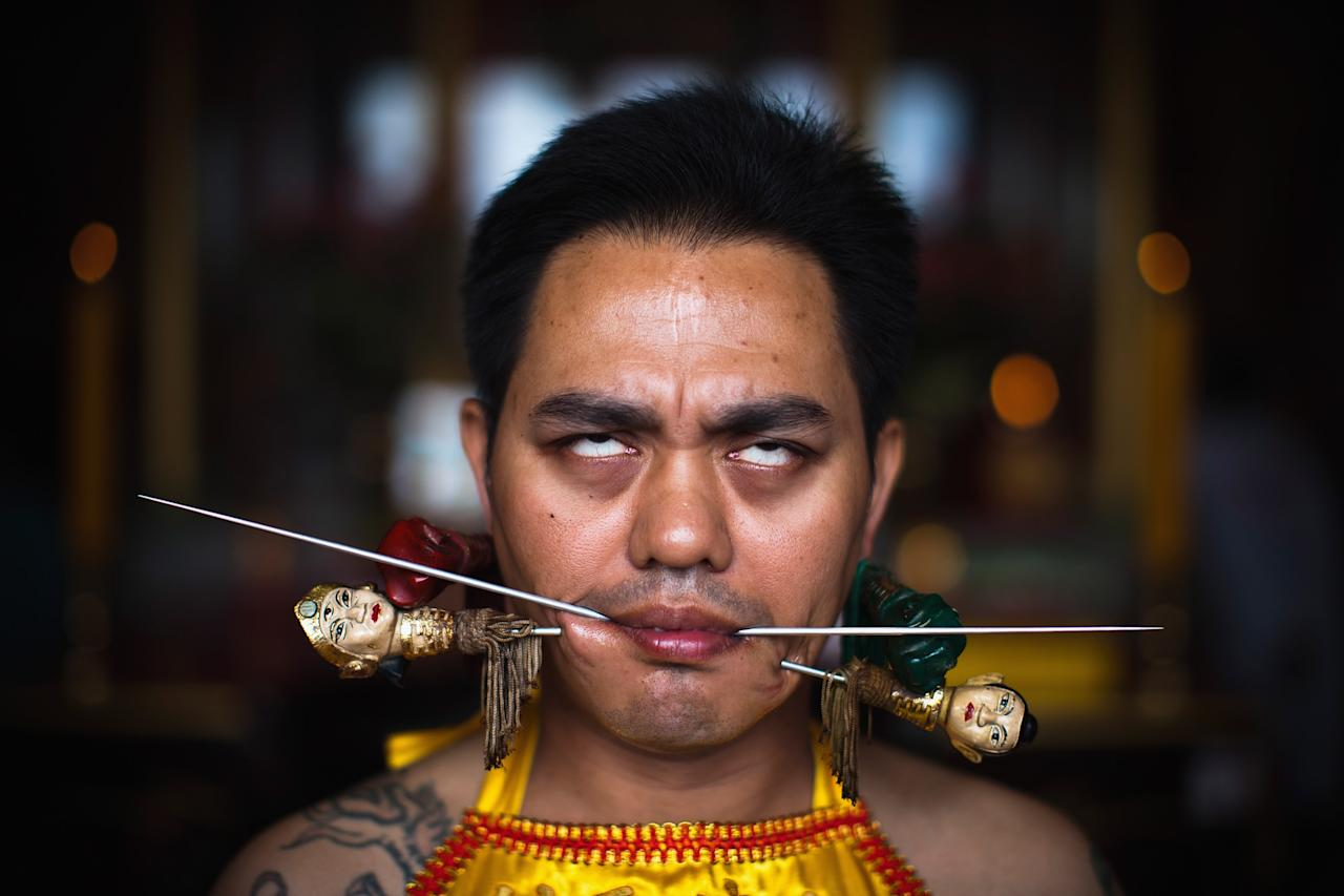 PHUKET, THAILAND - OCTOBER 05:  A devotee of the Chinese shrine of Sui Boon Tong Shrine, pierces his cheeks with skewers during a procession of Vegetarian Festival on October 5, 2011 in Phuket, Thailand. Ritual Vegetarianism in Phuket Island traces it roots back to the early 1800's. The festival begins on the first evening of the ninth lunar month and lasts for nine days. Participants in the festival perform acts of body piercing as a means of shifting evil spirits from individuals onto themselves and bring the community good luck.  (Photo by Athit Perawongmetha/Getty Images)