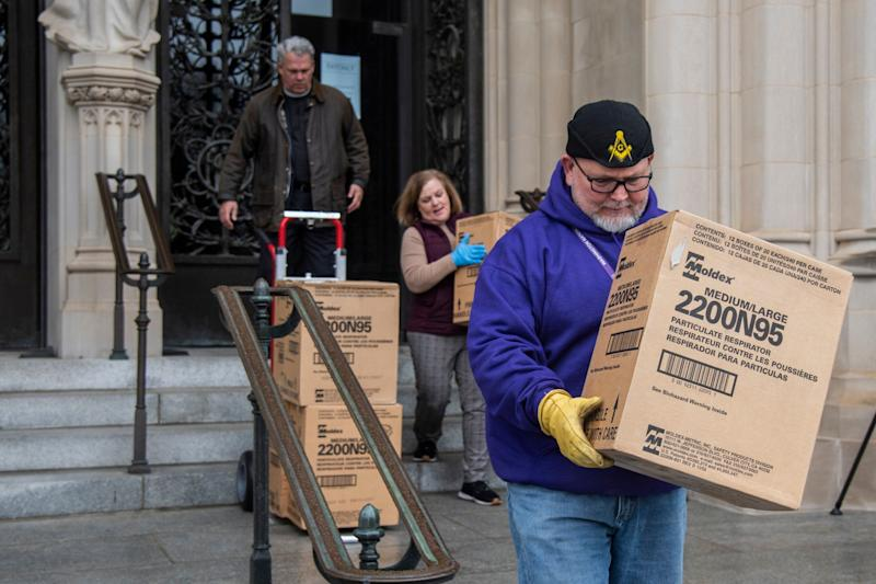 People transport boxes of N95 respirator masks out of the Washington National Cathedral on March 25, 2020. (Photo: The Washington Post via Getty Images)