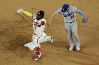 Atlanta Braves' Marcell Ozuna celebrates a RBI-double past Los Angeles Dodgers left fielder Enrique Hernandez during the sixth inning in Game 4 of a baseball National League Championship Series Thursday, Oct. 15, 2020, in Arlington, Texas. (AP Photo/David J. Phillip)
