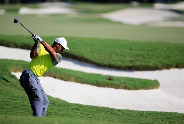 DORAL, FL - MARCH 07: Tiger Woods hits a shot on the 12th hole during the weather-delayed first round of the World Golf Championships-Cadillac Championship at Trump National Doral on March 7, 2014 in Doral, Florida. (Photo by Jamie Squire/Getty Images)