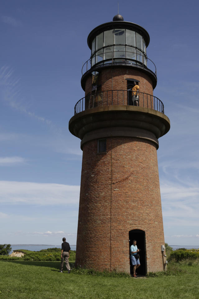 FILE - In this Aug. 27, 2009, file photo, President Barack Obama, left, walks around Gay Head Lighthouse while on vacation on Martha's Vineyard in Aquinnah, Mass. Thie lighthouse is on The National Trust for Historic Preservation 2013 list of 11 Most Endangered Historic Places. The lighthouse was the first lighthouse built on Martha's Vineyard in Massachusetts and now is in danger of toppling over the edge of the Gay Head Cliffs. Preservationists say it's threatened by a century of erosion at the oceanfront site and the impacts of climate change. (AP Photo/Alex Brandon, File)