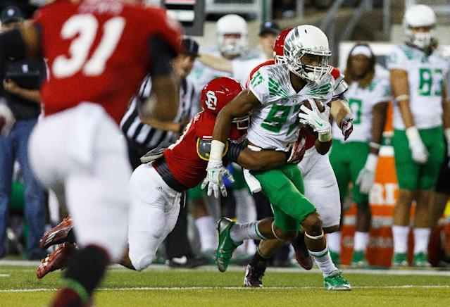 Oregon wide receiver Darren Carrington (87) runs downfield with a South Dakota defender's arms wrapped around him during the second quarter of an NCAA college football game in Eugene, Ore., Saturday, Aug. 30, 2014. (AP Photo/Ryan Kang)