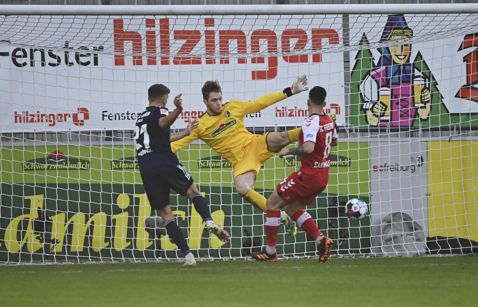 Berlin's Grischa Proemel, left, scores against Freiburg's goalkeeper Florian Mueller, center, the opening goal during the German Bundesliga soccer match between SC Freiburg and 1. FC Union Berlin in Freiburg, Germany, Saturday, Feb. 20, 2021. (Sebastian Gollnow/dpa via AP)