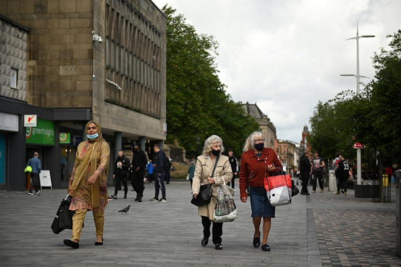 "People wear face masks as a precaution against the transmission of COVID-19 as they walk past closed shops in the centre of Bolton, northern England on September 9, 2020, as local lockdown restrictions are put in place due to a spike in cases of the novel coronavirus in the city. - The UK government, which controls health policy in England, imposed tougher restrictions on Bolton, near the northwest city of Manchester, after a ""very significant rise"" in cases. Bolton was found to have 120 cases per 100,000 people -- the highest in the country. (Photo by Oli SCARFF / AFP) (Photo by OLI SCARFF/AFP via Getty Images)"
