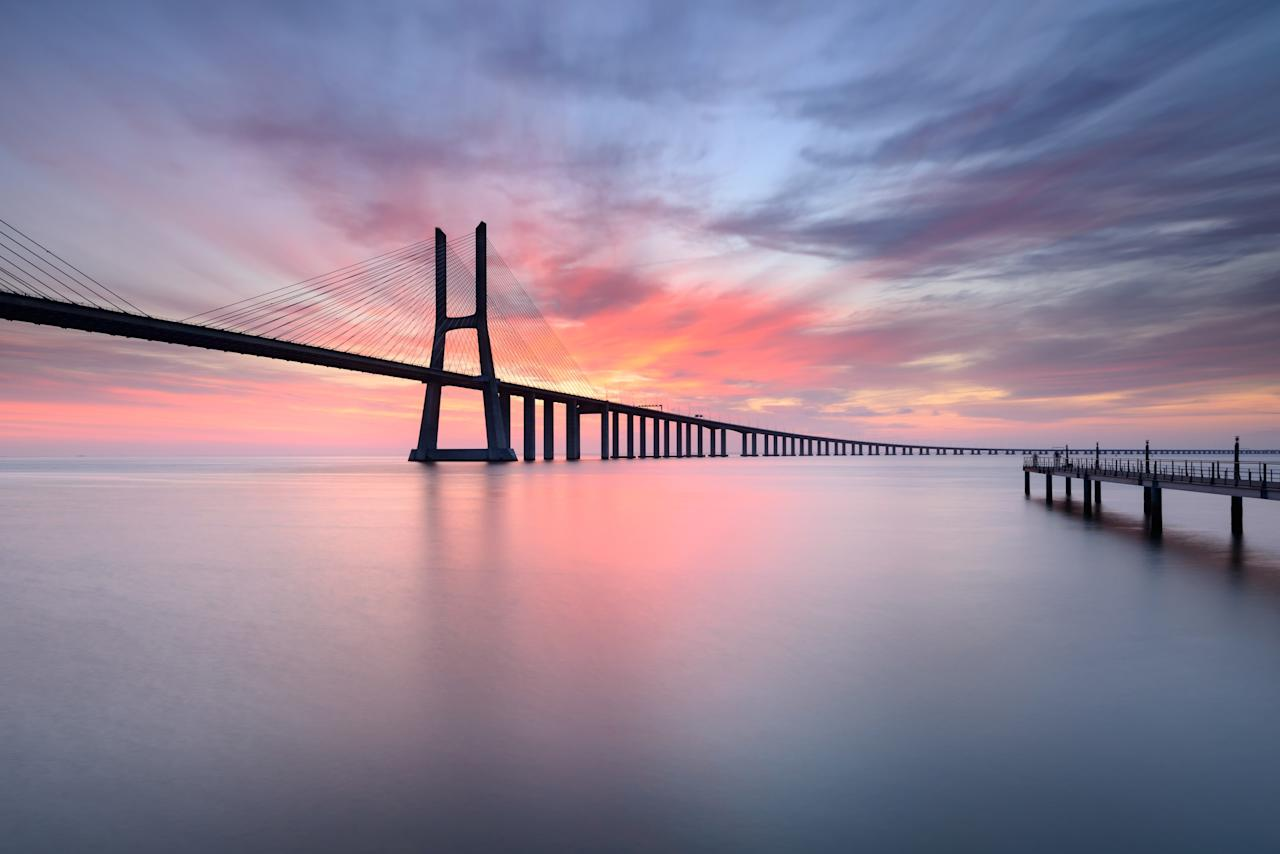 "Portugal's <strong>Vasco da Gama Bridge</strong> is not just an architectural marvel; it also provides great views of the surrounding waters of the Tagus River. Located in Lisbon, the bridge runs some 56,381 feet, and was completed in 1998.""/><figcaption>پل واسکودو گاما در پرتغال فقط یک مسیر برای عبور نیست ، یک تلفیق میان معماری و طبعیت محسوب می شود<br><br><br></figcaption></figure>    <figure class="