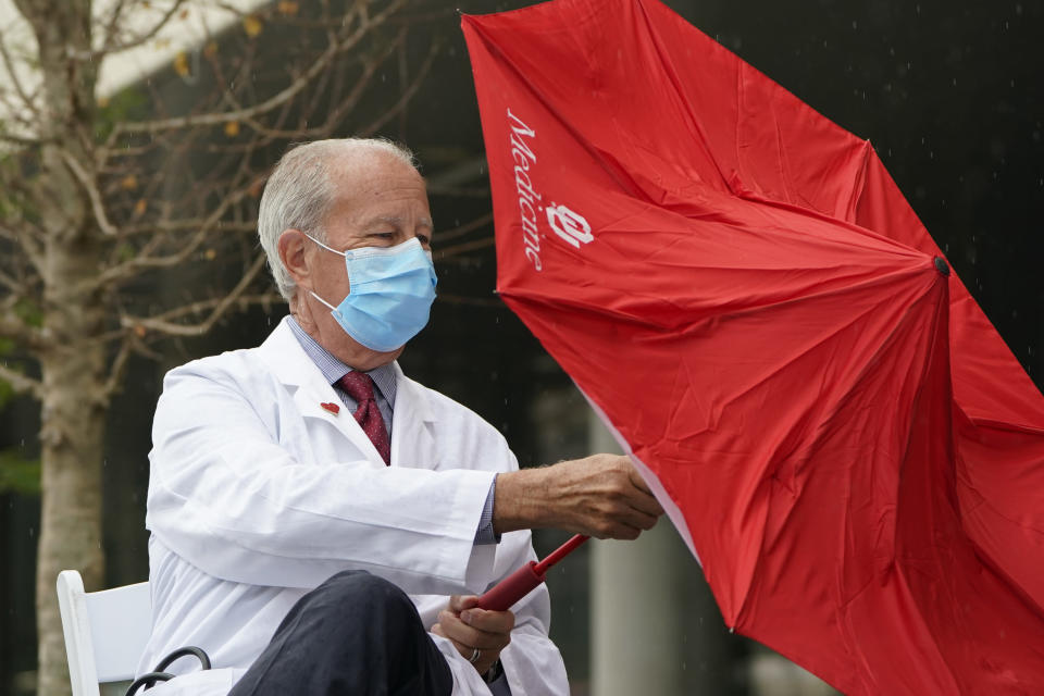 Dr. Dale Bratzler, OU Health Chief Quality Officer, opens an umbrella as it begins to shower during a joint news conference from Oklahoma City area health providers, Wednesday, Aug. 18, 2021, in Oklahoma City. (AP Photo/Sue Ogrocki)