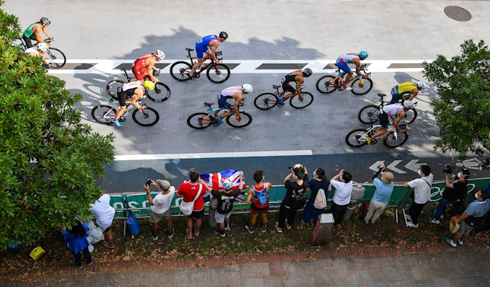 <p>A general view of the peleton as they pass spectators during the cycling discipline of the men's triathlon at the Odaiba Marine Park during the 2020 Tokyo Summer Olympic Games in Tokyo, Japan. (Photo By Ramsey Cardy/Sportsfile via Getty Images)</p>