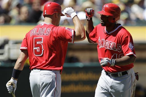 Los Angeles Angels' Torii Hunter, right, celebrates with Albert Pujols (5) after Hunter hit a home run off Oakland Athletics' Tommy Milone in the third inning of a baseball game, Monday, Sept. 3, 2012, in Oakland, Calif. (AP Photo/Ben Margot)