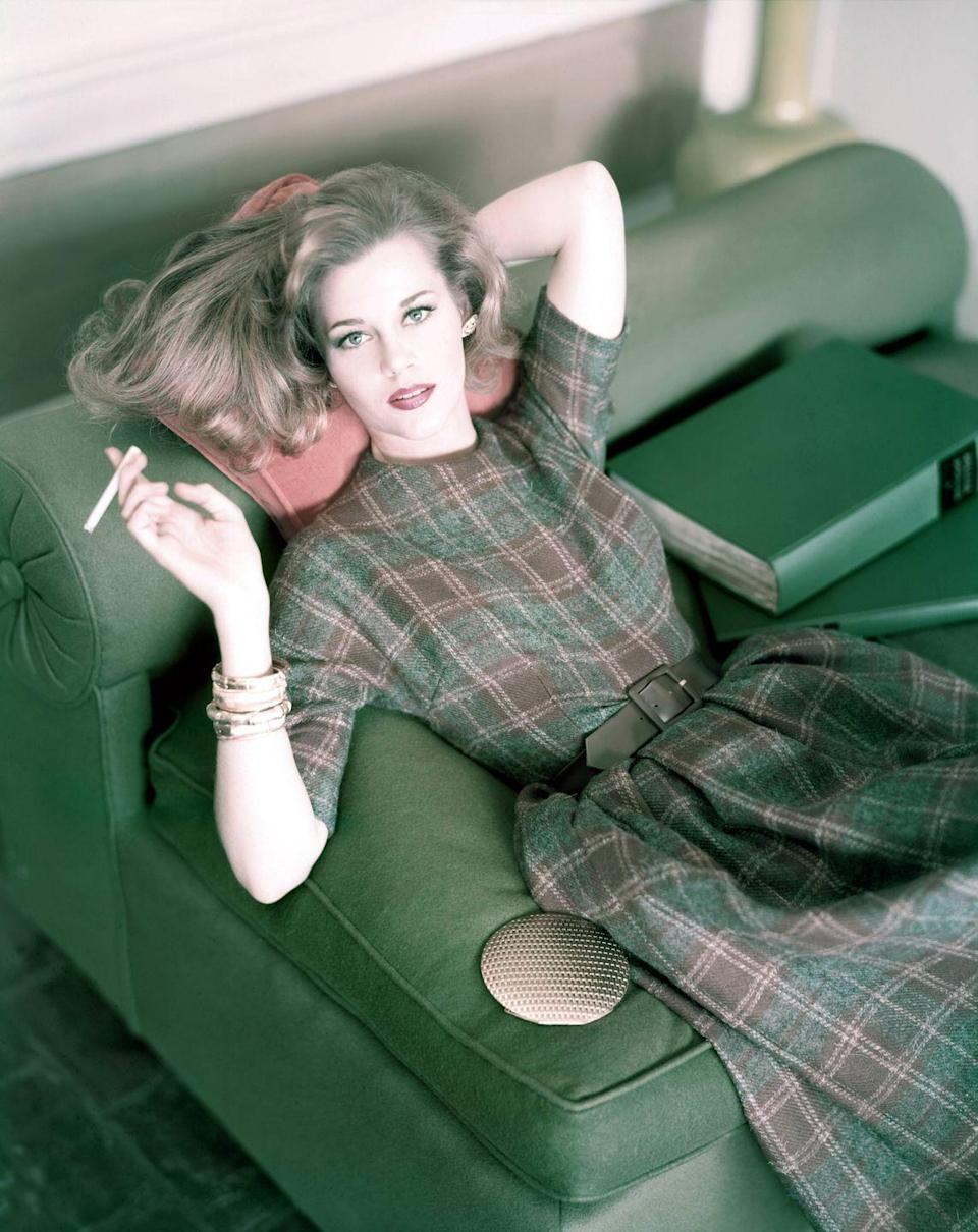<p>Jane Fonda poses for <em>Vogue</em> magazine holding a cigarette while wearing a plaid wool dress and brown suede belt. </p>