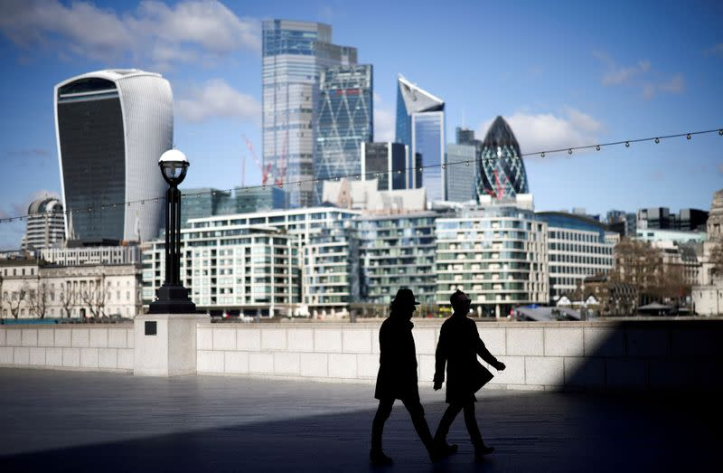 FILE PHOTO: The City of London financial district can be seen as people walk along the south side of the River Thames