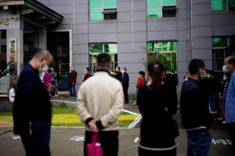People wearing face masks line up outside a community health centre for nucleic acid tests in Xianning, after the lockdown was eased in Hubei province