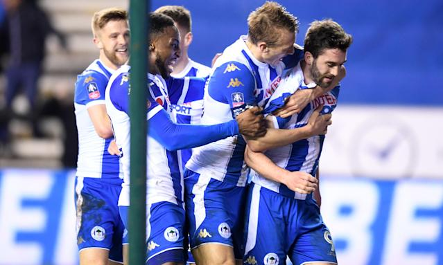 Will Grigg is mobbed by his team-mates after scoring Wigan's winner against Manchester City to reach the quarter-finals.