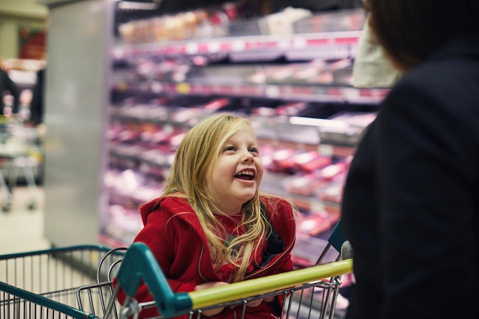 Happy smiling little girl sat in a shopping trolley while food shopping at the Supermarket