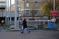 Dr. Philippe Montravers walks near the main entrance of the Bichat Hospital, in Paris on Tuesday, Nov. 10, 2020. Montravers and the 150 doctors and nurses he leads have become experts about how to treat COVID-19. That knowledge is proving invaluable against a second deadly surge of the virus is again threatening to overwhelm European health systems. (AP Photo/Francois Mori)