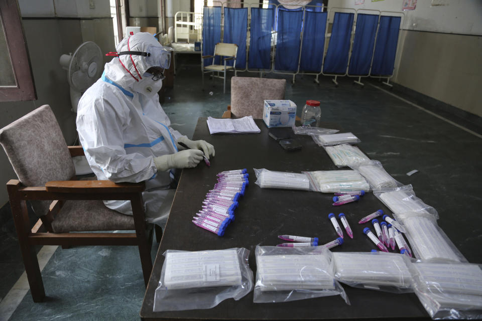 A health worker arranges swab samples of people to test for COVID-19 at a government hospital in Jammu, India, Thursday, Oct.29, 2020. India's confirmed coronavirus caseload surpassed 8 million on Thursday with daily infections dipping to the lowest level this week, as concerns grew over a major Hindu festival season and winter setting in. (AP Photo/Channi Anand)