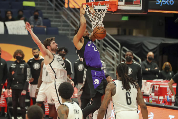 Toronto Raptors' Khem Birch, center, dunks past Brooklyn Nets' Joe Harris (12) during the second half of an NBA basketball game Wednesday, April 21, 2021, in Tampa, Fla. The Raptors won 114-103. (AP Photo/Mike Carlson)