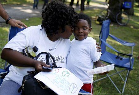 Protestor Irene Robinson (L) gets a hug from Terris Joshua outside Walter H. Dyett high school on the 11th day of her hunger strike in Chicago, Illinois, United States, August 27, 2015. REUTERS/Jim Young