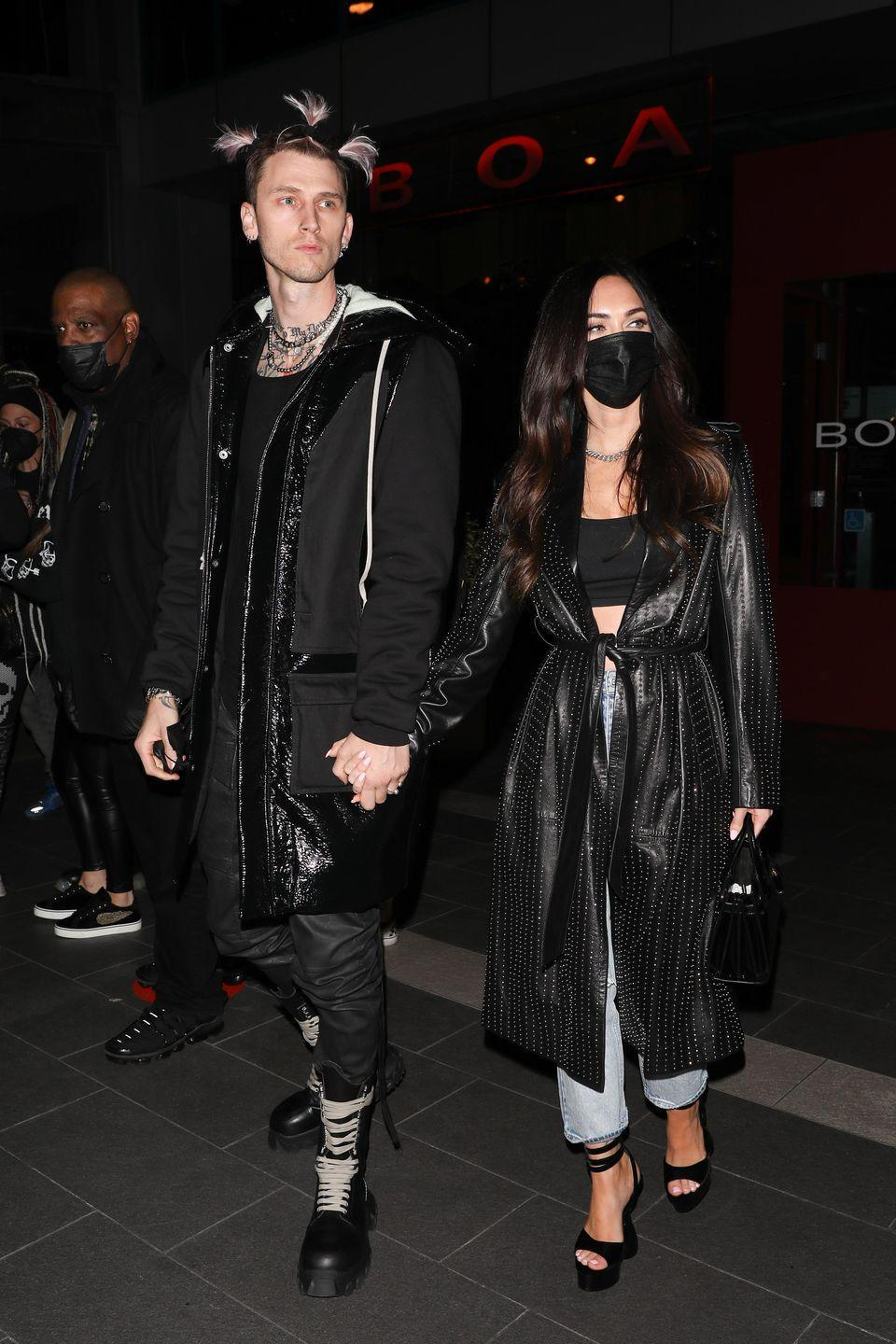 <p>Fox tied a long black leather coat over her black bralette, jeans and black heels, teamed with a black face mask while out with her partner. </p>