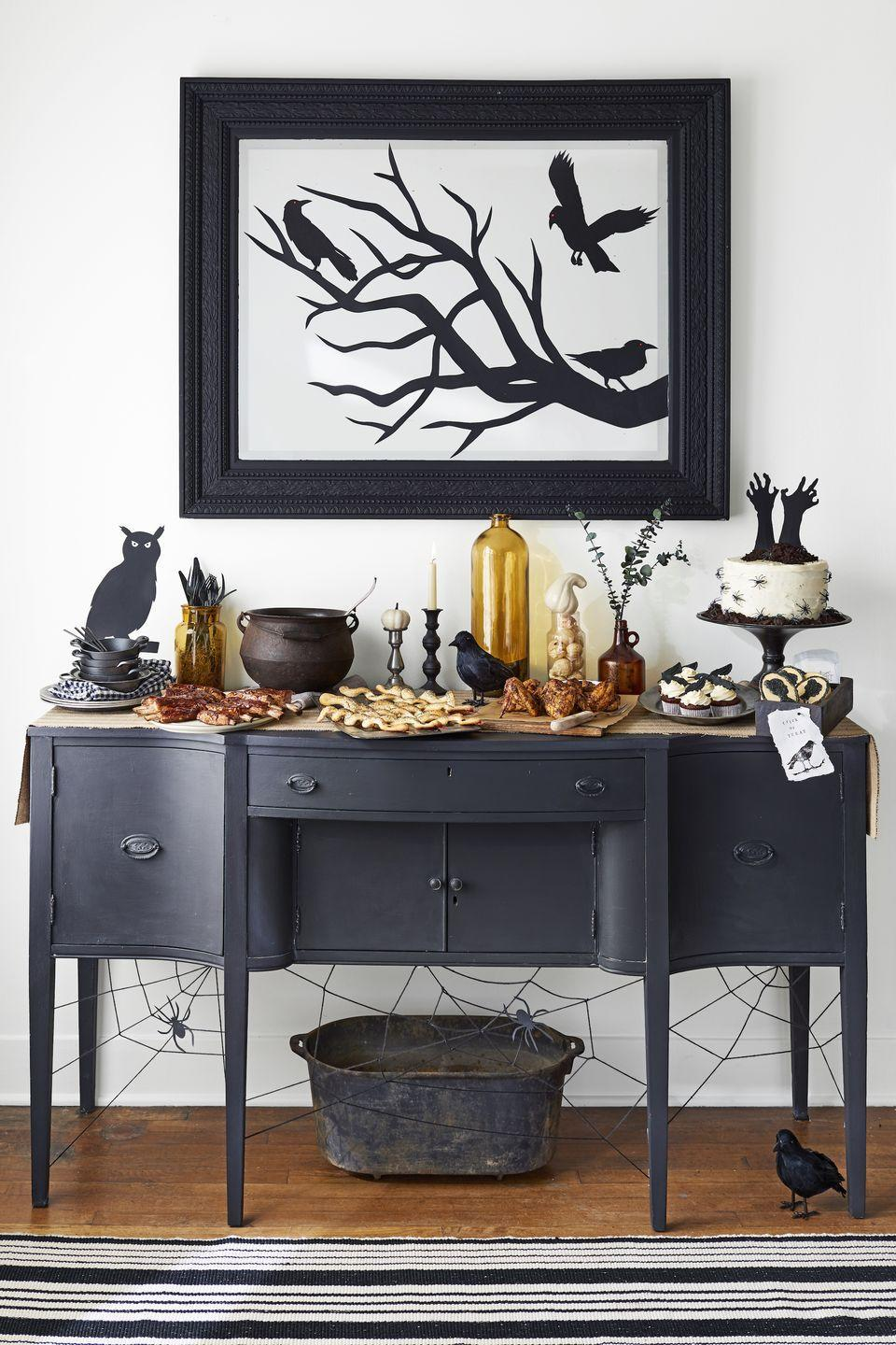 """<p>This shadowy party spread is giving us major Edgar Allen Poe vibes. Snip out branches and birds from black paper and adhere to a mirror or the walls with temporary glue dots.</p><p><em><a href=""""https://www.countryliving.com/entertaining/g271/halloween-decorating-1005"""" rel=""""nofollow noopener"""" target=""""_blank"""" data-ylk=""""slk:Get the tutorial at Country Living »"""" class=""""link rapid-noclick-resp"""">Get the tutorial at Country Living »</a></em> </p>"""