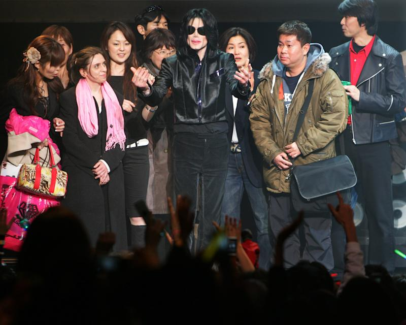 "FILE - In this March 9, 2007 file photo, U.S. pop singer Michael Jackson greets his fans during an event ""Fan Appreciation Day"" in Tokyo. Michael Jackson's estate is suing a man and three companies in Japan, alleging they are using the name and likeness of the late pop star on key chains, mugs and other products without permission. The lawsuit filed in Tokyo District Court last month, Sept. 2013, does not seek money but demands the actions stop. It names Ryosuke Matsuura and three companies, Michael Jackson Asian Rights, Michael Jackson Enterprises and Michael Jackson World. (AP Photo/Itsuo Inouye, File)"