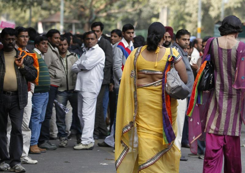 Indian men watch participants walk during the 5th Delhi Queer Pride parade in New Delhi, India, Sunday, Nov. 25, 2012. Hundreds of gay rights activists marched through New Delhi on Sunday to demand that they be allowed to lead lives of dignity in India's deeply conservative society.(AP Photo/ Mustafa Quraishi)