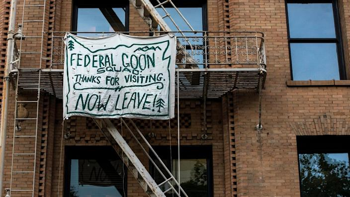 People in Portland have been hanging banners aimed at federal officers from their balconies