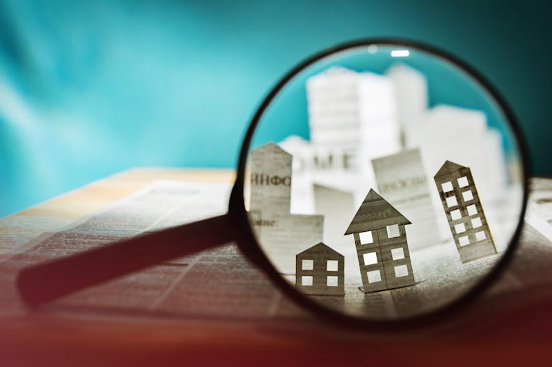 Magnifying glass in front of an open newspaper with paper houses. Concept of rent, search, purchase real estate. Photo: Getty