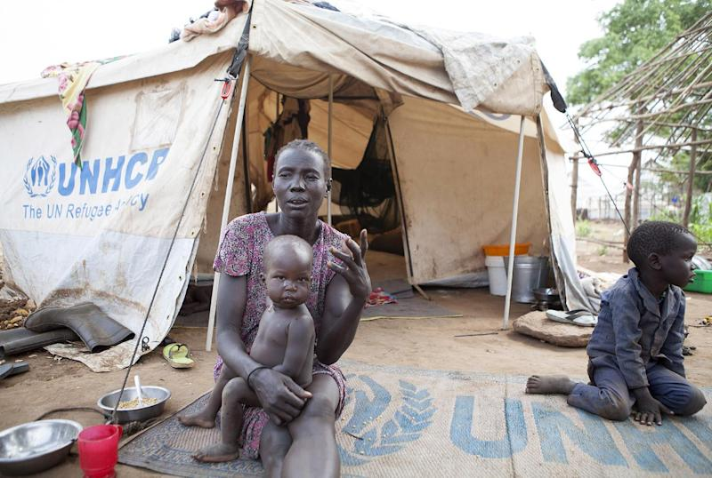 A woman and her children displaced by fighting in South Sudan sit outside her tent at the Kule camp for Internally Displaced People at the Pagak border crossing in Gambella, Ethiopia, on July 10, 2014 (AFP Photo/Zacharias Abubeker)