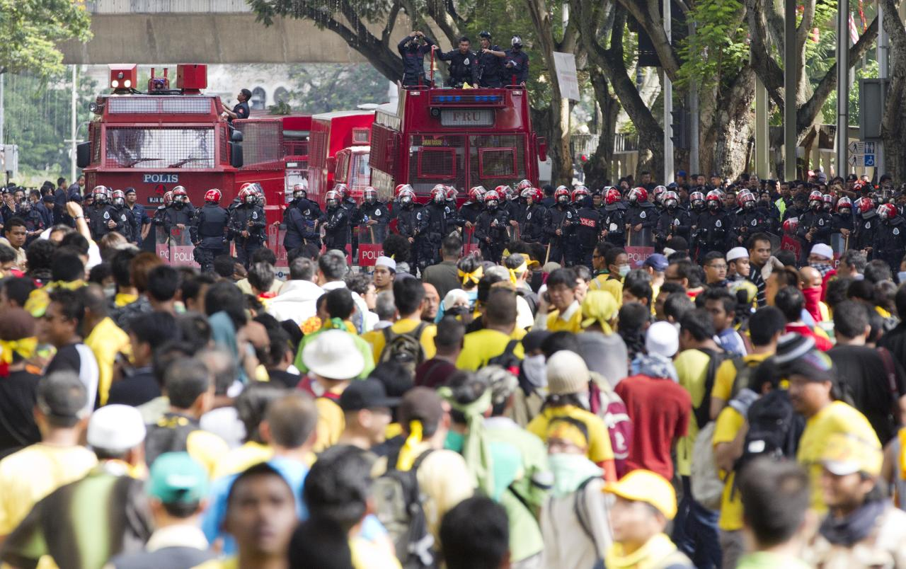 Malaysian riot police form a barricade to stop protesters in Kuala Lumpur, Malaysia, Saturday, April 28, 2012. Malaysian police fired tear gas and chemical-laced water Saturday at thousands of demonstrators demanding an overhaul in electoral policies that they call biased ahead of national polls expected soon. At least 25,000 demonstrators had swamped Malaysia's largest city in one of the Southeast Asian nation's biggest street rallies in the past decade. (AP Photo/Mark Baker)