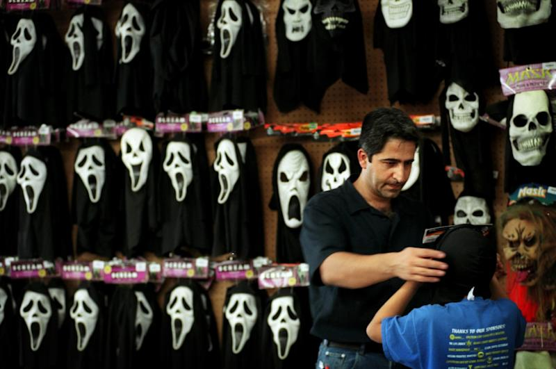 """A man places a """"Scream"""" mask on his son at a Spirit Halloween store"""