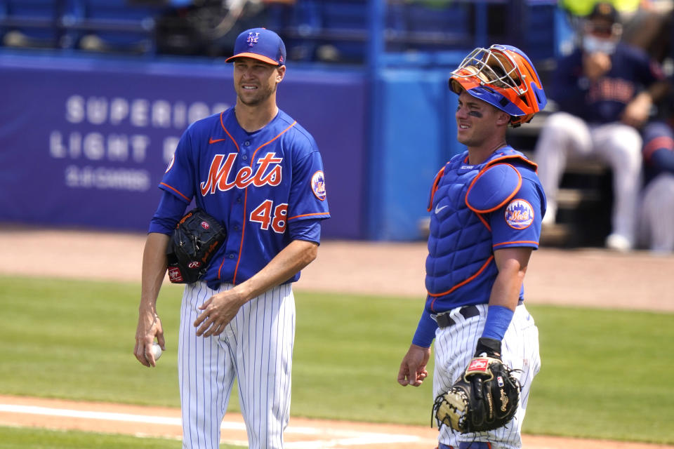 New York Mets starting pitcher Jacob deGrom (48) talks with catcher James McCann during the fourth inning of a spring training baseball game against the Houston Astros, Tuesday, March 16, 2021, in Port St. Lucie, Fla. (AP Photo/Lynne Sladky)