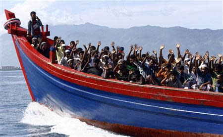 File picture shows ethnic Rohingya refugees from Myanmar waving as they are transported by a wooden boat to a temporary shelter in Krueng Raya in Aceh Besar