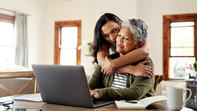 Cropped shot of an attractive young woman hugging her grandmother before helping her with her finances on a laptop.