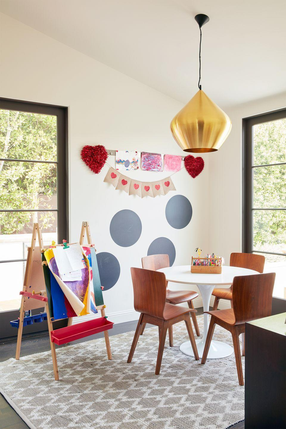 """<p>Kids need a place to let their imaginations soar, too. But they also need a designated place to organize all their markers, pens, paintbrushes, and papers, so make sure you invest in some items that keep it all in one place. An easel with built-in storage for pens, plus a <a href=""""https://www.containerstore.com/s/craft-hobby/artbin-double-deep-super-satchel/1d"""" rel=""""nofollow noopener"""" target=""""_blank"""" data-ylk=""""slk:portable carrier"""" class=""""link rapid-noclick-resp"""">portable carrier</a> to go on the table, and some hooks or a <a href=""""https://www.wayfair.com/Dotted-Line%E2%84%A2--Bambi-Craft-Wall-Mount-Thread-Store-X112670710-L2555-K~W001235852.html"""" rel=""""nofollow noopener"""" target=""""_blank"""" data-ylk=""""slk:wall unit"""" class=""""link rapid-noclick-resp"""">wall unit</a> to hang the finished products on display, as seen in this kid-friendly craft room by <a href=""""https://www.natashabaradaran.com/"""" rel=""""nofollow noopener"""" target=""""_blank"""" data-ylk=""""slk:Natasha Baradaran"""" class=""""link rapid-noclick-resp"""">Natasha Baradaran</a>, are all great ideas. </p>"""