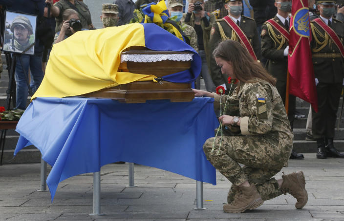 FILE - In this July 14, 2020, file photo, a Ukrainian soldier pays her final respects at the coffin of serviceman Taras Matviiv, honored with the Hero of Ukraine highest state award after being killed while fighting against pro-Russian rebels, during his funeral in Independence Square, Kyiv, Ukraine. Tensions have risen in the conflict in eastern Ukraine, with growing violations of a cease-fire and a massive Russian military buildup on its side of the border. (AP Photo/Efrem Lukatsky, File)