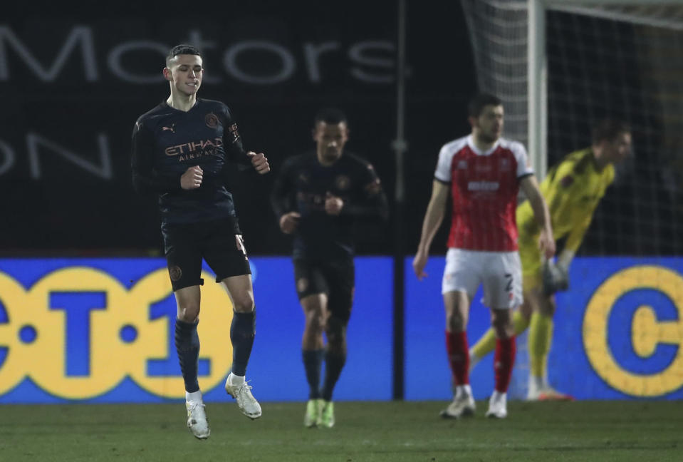 Manchester City's Phil Foden, left, celebrates after scoring his sides 1st goal of the game during the English FA Cup fourth round soccer match between Cheltenham Town and Manchester City at the Jonny-Rocks stadium in Cheltenham, England Saturday, Jan. 23, 2021. (Nick Potts /Pool via AP)