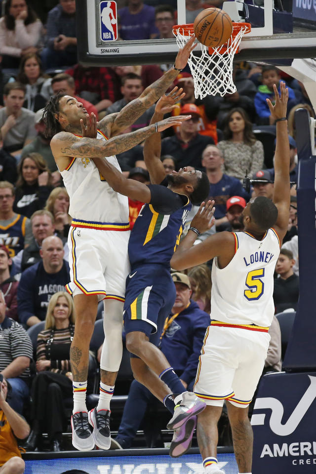 Golden State Warriors center Willie Cauley-Stein, left, blocks the shot of Utah Jazz guard Emmanuel Mudiay, center, as Golden State Warriors forward Kevon Looney (5) defends in the first half during an NBA basketball Friday, Dec. 13, 2019, in Salt Lake City. (AP Photo/Rick Bowmer)