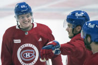 Montreal Canadiens' Cole Caufield (22) smiles as he talks with teammate Nick Suzuki (14) during practice in Brossard, Quebec, Sunday, June 27, 2021. The Canadiens take on the Tampa Bay Lightning in the NHL hockey Stanley Cup finals beginning Monday in Tampa, Fla. (Graham Hughes/The Canadian Press via AP)