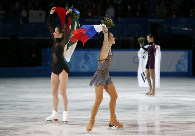 Russia's Adelina Sotnikova (C), Korea's Yuna Kim (R) and Italy's Carolina Kostner celebrate with their flags after the flower ceremony during the Figure Skating Women's free skating Program at the Sochi 2014 Winter Olympics, February 20, 2014. REUTERS/Lucy Nicholson (RUSSIA - Tags: OLYMPICS SPORT FIGURE SKATING)