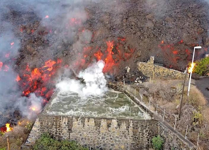Hot lava reaches a balsa normally used for for irrigation after an eruption of a volcano on the island of La Palma in the Canaries, Spain, Monday Sept. 20, 2021. Giant rivers of lava are tumbling slowly but relentlessly toward the sea after a volcano erupted on a Spanish island off northwest Africa. The lava is destroying everything in its path but prompt evacuations helped avoid casualties after Sunday's eruption.