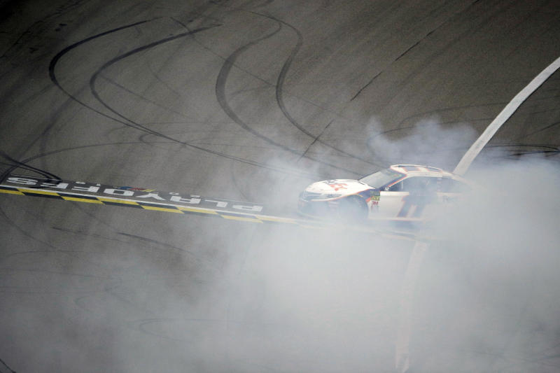 Denny Hamlin does a burnout after winning a NASCAR Cup Series auto race at Kansas Speedway in Kansas City, Kan. Sunday, Oct. 20, 2019. (AP Photo/Charlie Riedel)