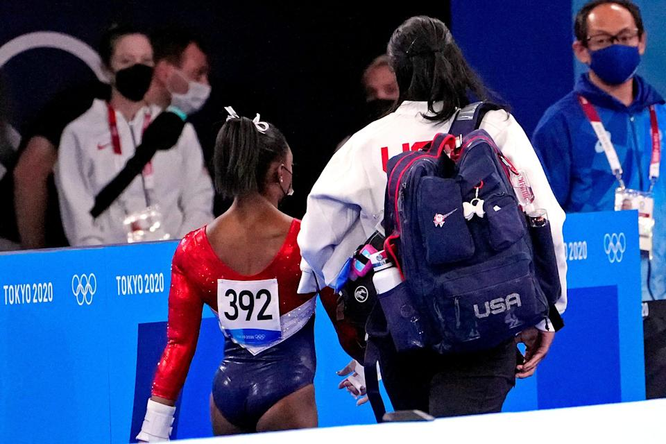 Simone Biles walks off the floor with her trainer after the first rotation.