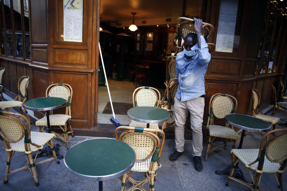 A cafe employee carries chairs as he setting up a terrace, in Paris, Tuesday, June 2, 2020. Parisians who have been cooped up for months with take-out food and coffee will be able to savor their steaks tartare in the fresh air and cobbled streets of the City of Light once more -- albeit in smaller numbers. (AP Photo/Thibault Camus)
